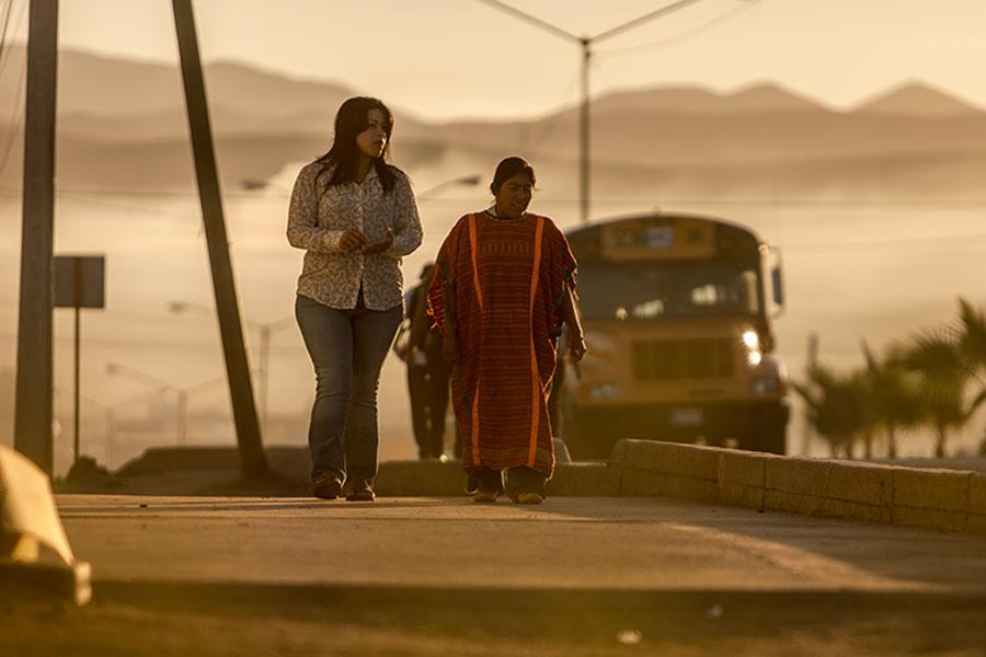 Amelia walks along the street with a Triqui woman.
